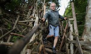 Lars Vilks in Sweden standing on a wood scuplture