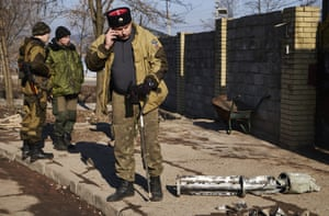The detritus of war is seen everywhere: a Cossack officer makes a phone call beside the remains of a missile outside his base in Donetsk.