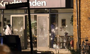 Police examine the bullet-marked cafe where the first attack took place.