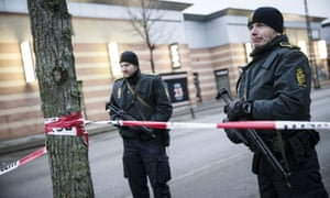 Police survey a street near the site where a man has been shot in Copenhagen.