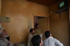 Pakistani shopkeepers watch in Rawalpindi