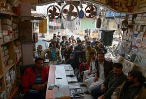 Pakistani shopkeepers and residents watch at a market in Rawalpindi.