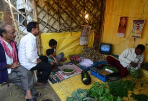 Indian cricket fans sit at vegetable stall in Allahabad.