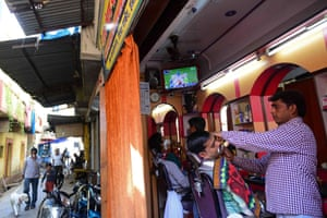 Indian customers get a shave and watch the game at a barbershop in Allahabad.