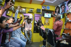 Indian cricket fans react and pose at a barbershop in Hyderabad.