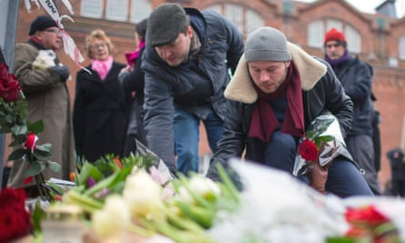 People place flowers close to the scene of the cafe shooting in Oesterbroin in Copenhagen.