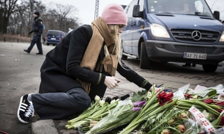 Woman lays flowers at Copenhagen synagogue