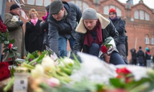 People place flowers close to the scene of the cafe shooting.