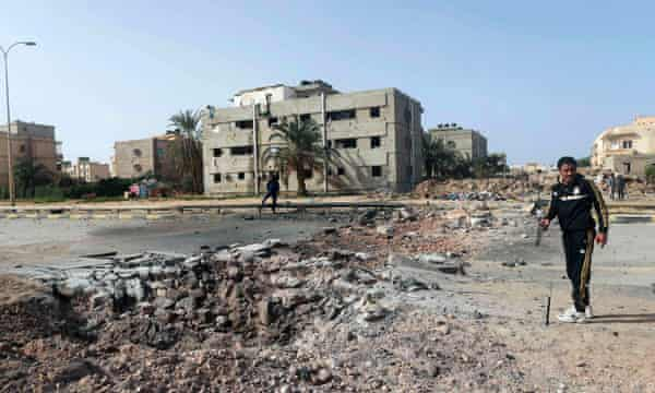 People stand near the site of an explosion in Benghazi. A car laden with explosives killed two people, as well as the driver, and wounded around 20.