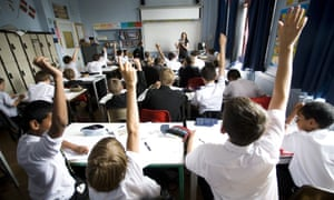 Schoolchildren raise their hands to answer questions in a classroom.