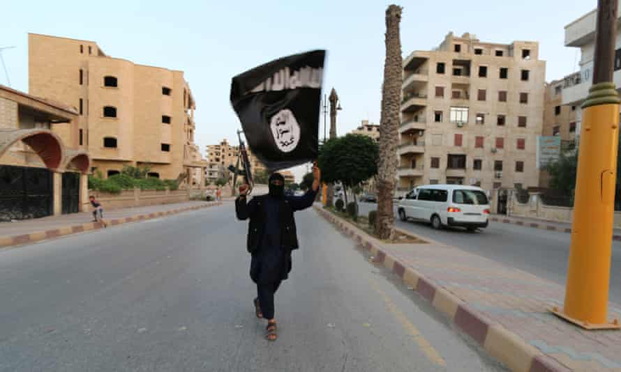 An Islamic State fighter waves a flag in Raqqa.