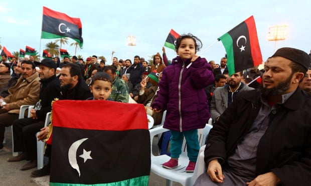Libyans wave national flags on Martyrs' Square in Tripoli as hundreds of people demonstrated in support of the UN-brokered dialogue between warring factions.