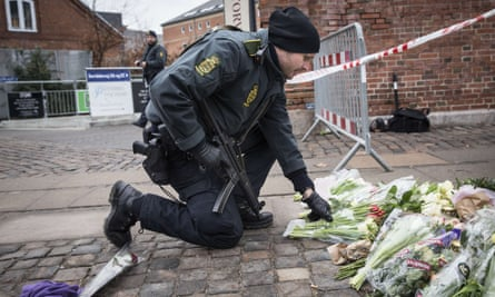 A police officer lays flowers outside the main Synagogue in Copenhagen following the fatal attacks in the Danish capital