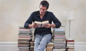 Man sitting on seat made from books