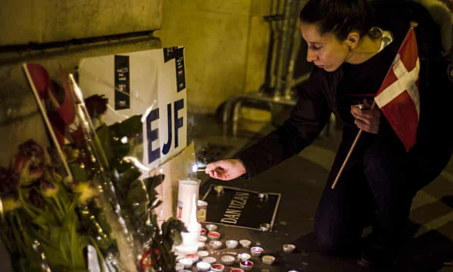 A woman lights a candle in front of the Danish embassy  following the terrorist attack in Copenhagen