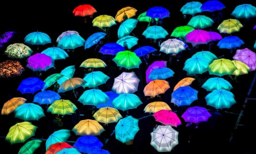 Luminous umbrellas lit beneath high wire artist Jade Kindar-Martin.