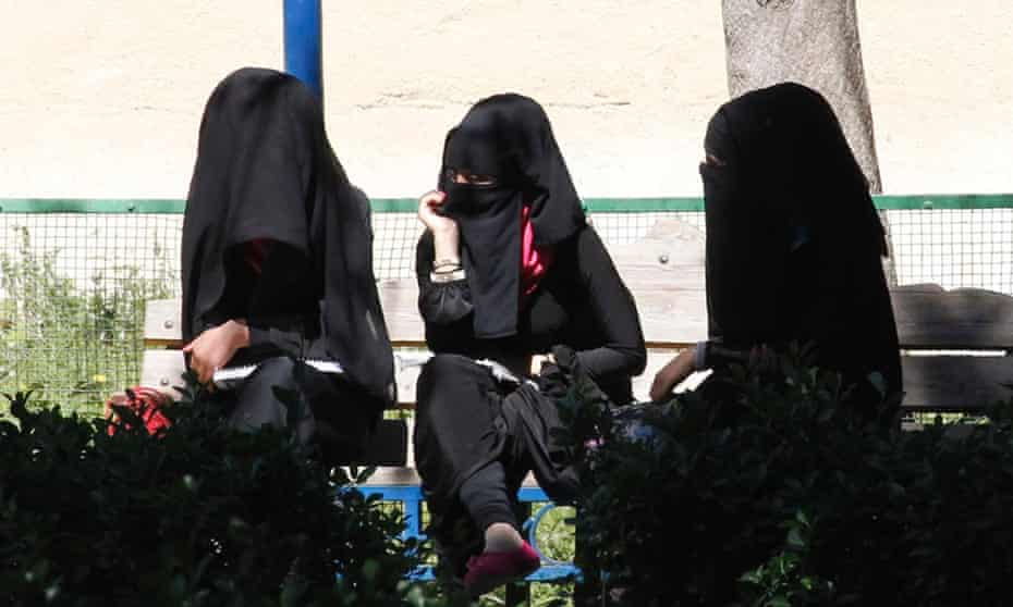 Veiled women sit on a bench in Raqqa
