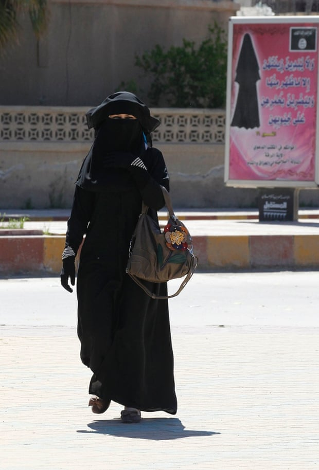 A veiled woman walks past a billboard urging women to wear a hijab