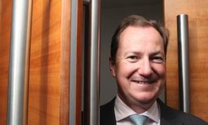 portrait of smiling Philip Monks between set of double doors