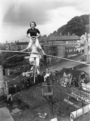 15 year old Elsie Davis practising a balancing act above her garden with her father and brother, who have left their jobs as miners to join a circus.