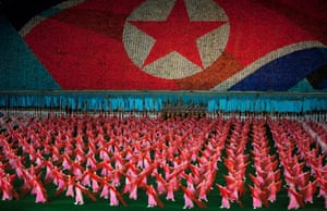 North Korean women dance in front their nation's flag, made by thousands of people holding coloured cards