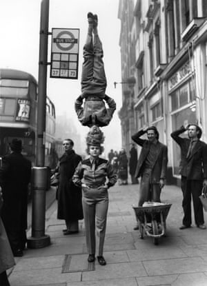 Passers-by stop and stare as two members of the Bertram Mills Circus walk along the pavement at Hammersmith Broadway, one supporting the other on her head.