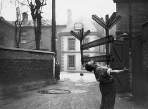 28th March 1936: Mr Joe Smith, a blacksmith strongman from Gloucester performs an amazing feat of strength, picking up and balancing a roadworks notice in his teeth.