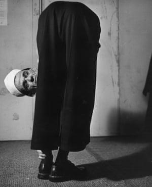 circa 1953: Eddie Merky folds himself in half and peers round his legs.