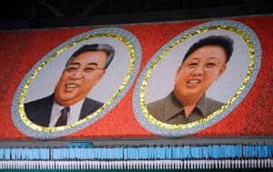 Portraits of late North Korean leaders Kim Jong-il and Kim Il-sung (L) form the background