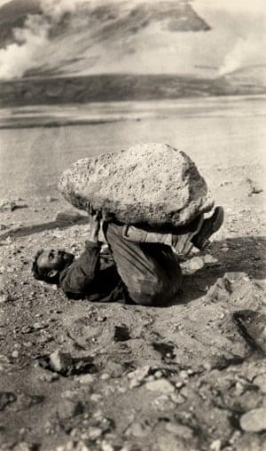 1st Sep 1921: A man balances a piece of pumice rock on his legs.