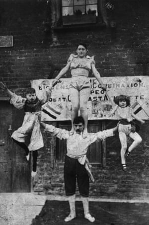 circa 1890: A street artiste balancing a woman and a couple of children from each arm and his shoulders.
