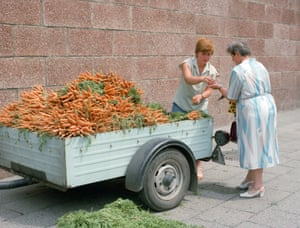 A trader in East Berlin sells her only ware, carrots, from a cart.