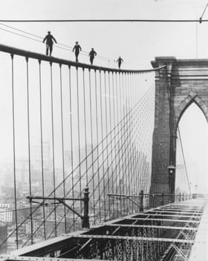 Four men climbing Brooklyn Bridge in New York City as part of a test for applicants wishing to be appointed to paint the bridge.