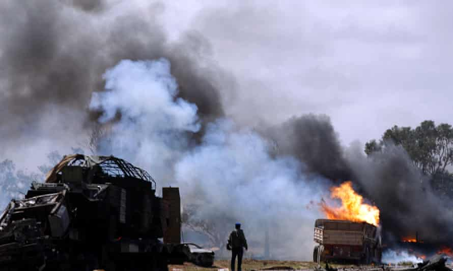 A Libyan rebel fighter looks at burning vehicles belonging to forces loyal to Gaddafi after an air strike by coalition forces in 2011.