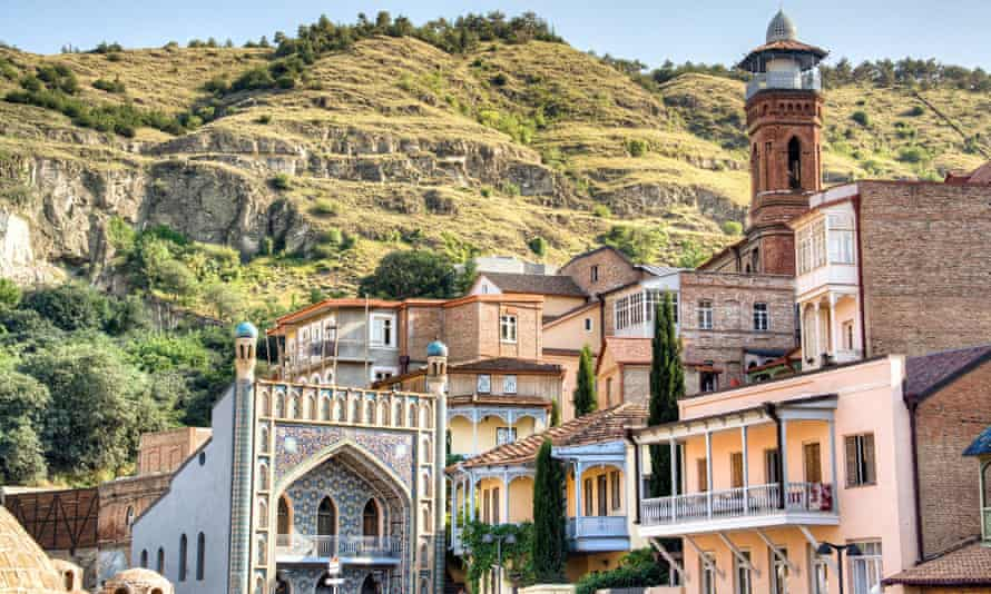 ornate buildings of Tbilisi with hills behind
