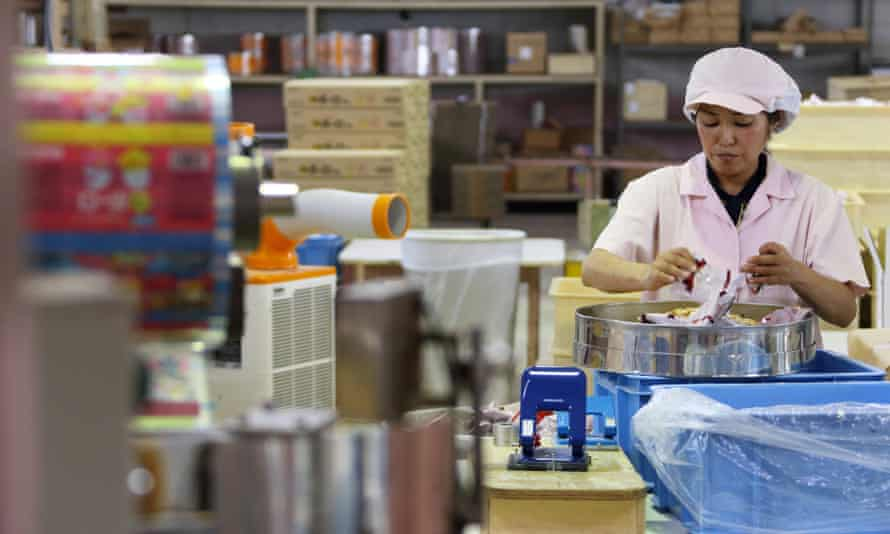 A worker inspects packets of egg biscuits on a production line in a factory in Inuyama, Aichi Prefecture, Japan.