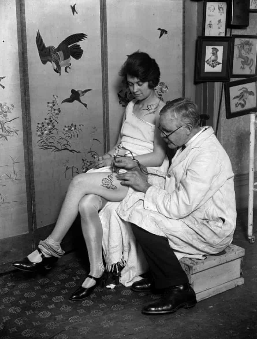 March 1928:  A woman having an image of a snake tattooed onto her thigh by tattooist, George Burchett.