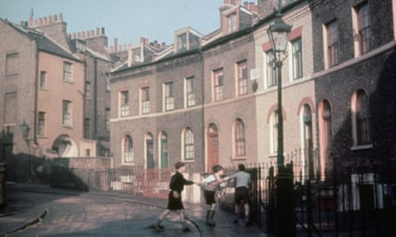 Three boys playing on a street of terraced houses in London, 1953.
