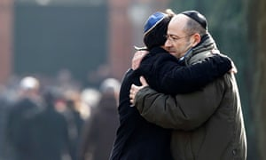 Men embrace at the funeral of security guard Dan Uzan