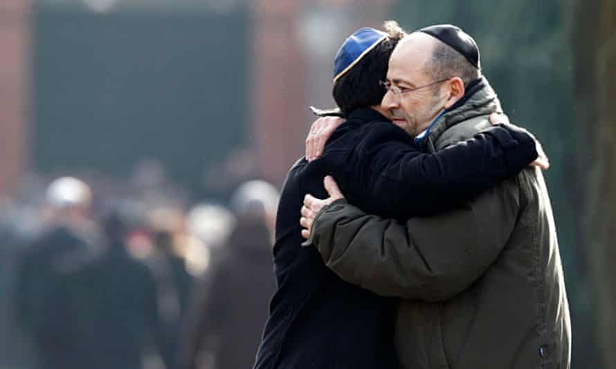 Men embrace at the funeral of security guard Dan Uzan