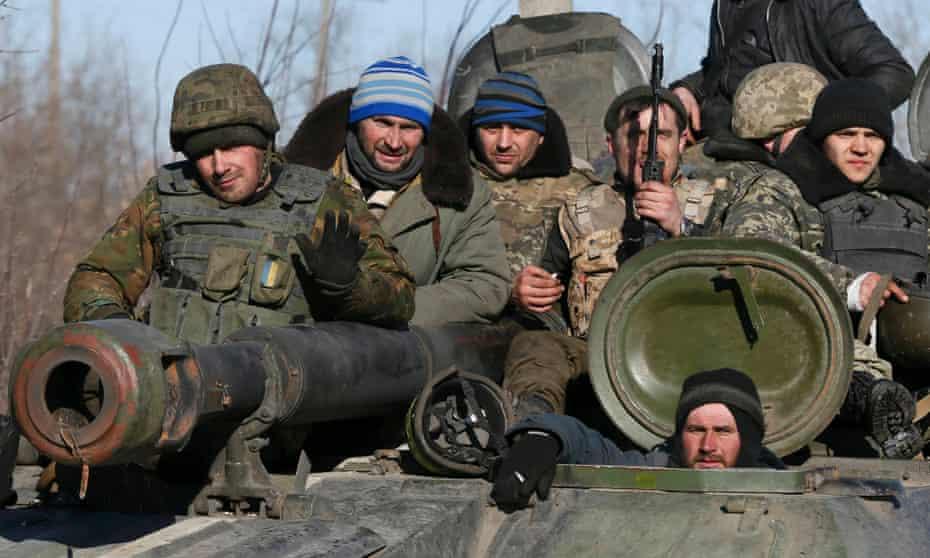 Fatigue in retreat: Ukrainian servicemen sit on top of a tank near Artemivsk, as they withdraw from Debaltseve following a fierce offensive by Russian-backed separatists.