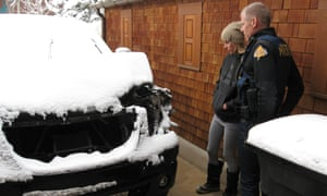 In this photo taken on 29 December 2014 and provided by the Aspen police department, Anna Hansen, girlfriend of Lance Armstrong, and Aspen police officer Rick Magnuson look over the damage to Armstrong's vehicle.