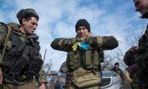 Pro-Russia fighters tear apart a Ukrainian flag
