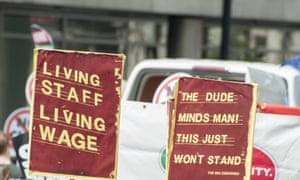 Campaigners with banners reading 'Living Staff, Living Wage' at a London demonstration.