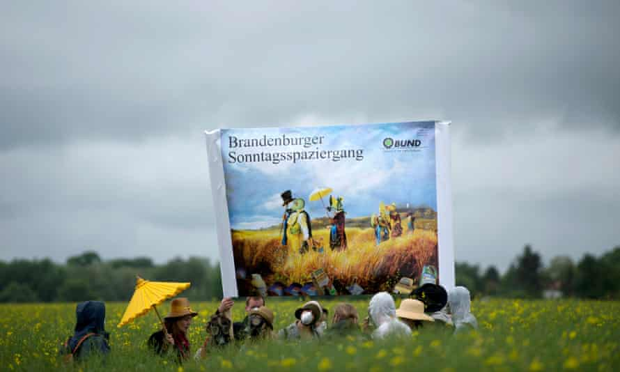 Environmental activists stand with respirator masks in a canola field during the campaign 'No poison on our fields' ('Kein Gift auf unsere Felder') near Fahrland, Germany, 22 May 2013. The acitivists fight for mandatory goals and measures for the reduction of pesticides in agriculture and demand the introduction of a tax on pesticides.