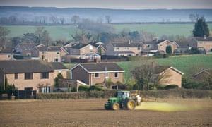 A crop sprayer applying pesticide close to residential housing