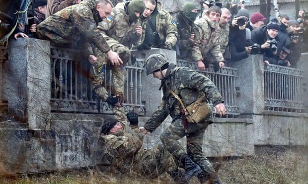 A guard tries to arrest a fighter of the Ayda Ukrainian volunteer battalion in Kiev