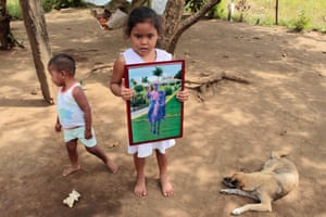 The girl holds a photograph of her grandfather who worked as a sugarcane cutter and died nine years ago of chronic renal failure.