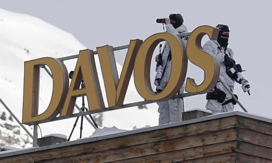 Armed Swiss police officers stand guard on the roof of a hotel the day before the opening of the Wor