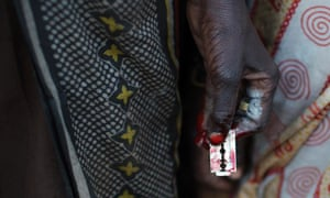 A woman holds a razor blade after performing a circumcision on four girls in a village in Kenya